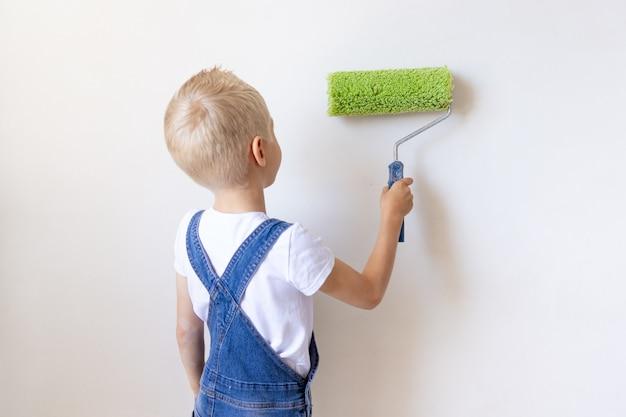 子供男の子ビルダーはアパートのローラーで白い壁を塗る、子供は家の修理、背面図、テキストの場所を作る
