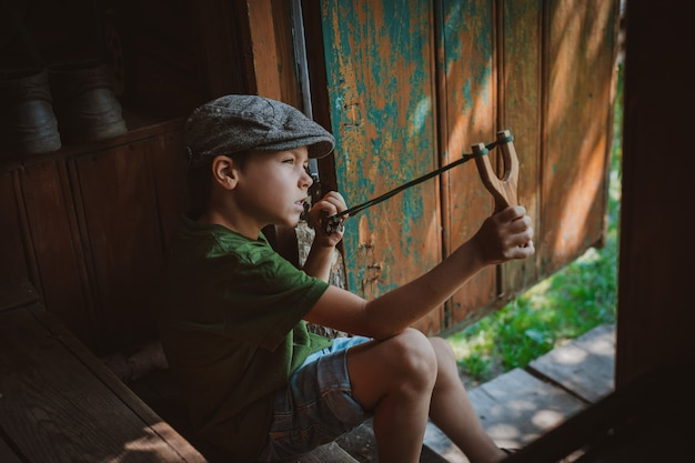 Child boy in a cap takes aim with a slingshot to shoot at a target. play around as a child in the village on vacation.