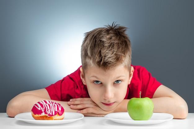 子供男の子は、ドーナツと青リンゴから選択します。誘惑、ファーストフード、健康食品、ダイエットに対する概念の抵抗。