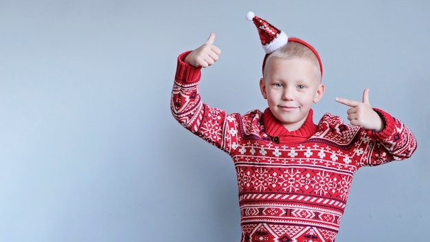 Child, boy in christmas red hat and sweater on gray background. new year and x-mas concept.