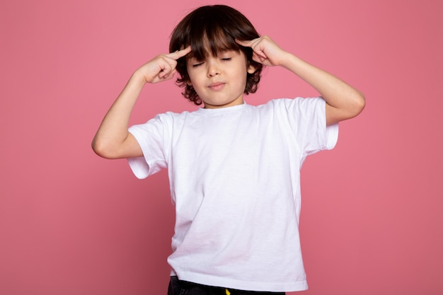 Child boy cute adorable portrait in white t-shirt and black trousers on pink desk
