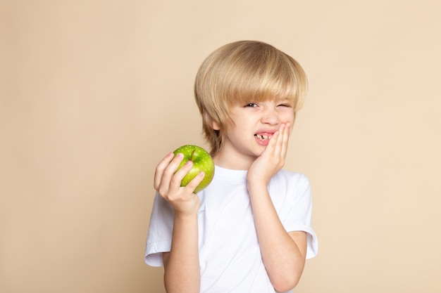 Child boy cute holding green apple in white t-shirt on pink