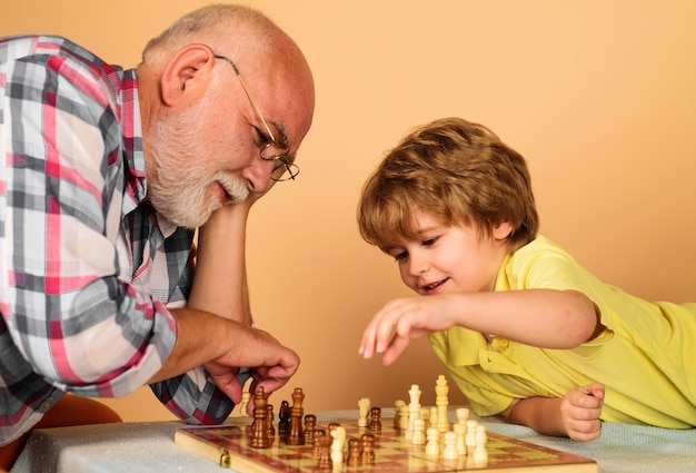 Child boy developing chess strategy. grandfather and grandson playing chess. brain development and logic concept.