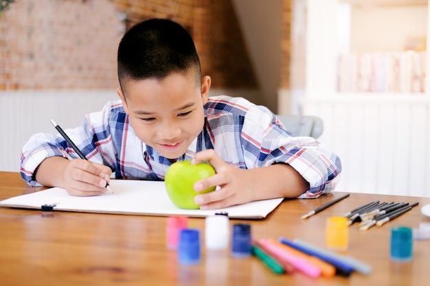 子供の男の子が家で絵を描いています。