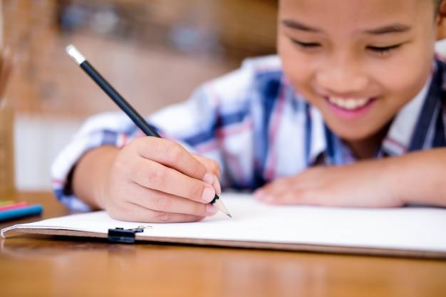 子供男の子が自宅で絵を描きます。