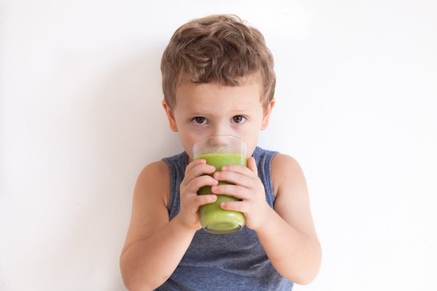 Child (boy) drinking healthy green vegetable smoothie - healthy eating, vegan, vegetarian, organic food and drink concept. summer drinks.