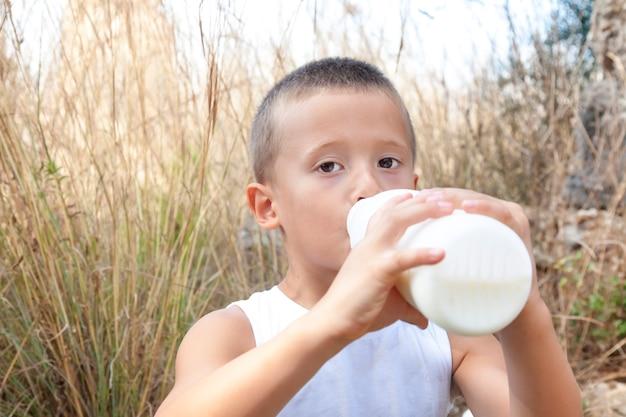 子供の男の子は、野原や草の背景にボトルから牛乳や乳飲料を飲みます。