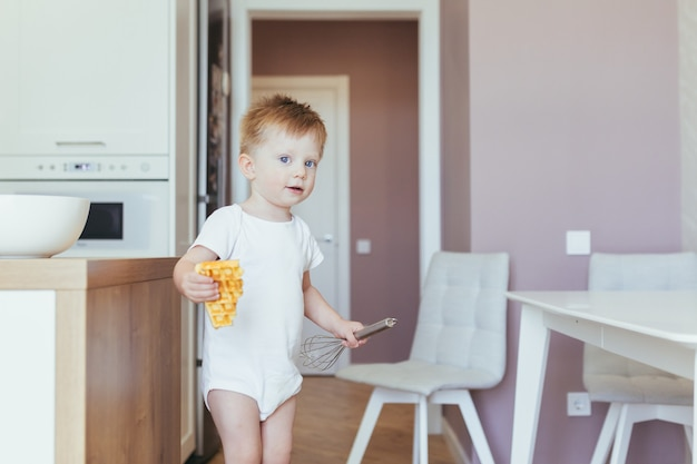 Child boy eats breakfast in the morning at home in the kitchen