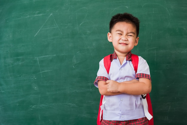 Child boy from kindergarten in student uniform with school bag stand smiling on school blackboard
