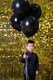 金の光沢のあるスパンコールのパレットと背景に黒い風船を保持している子供の男の子