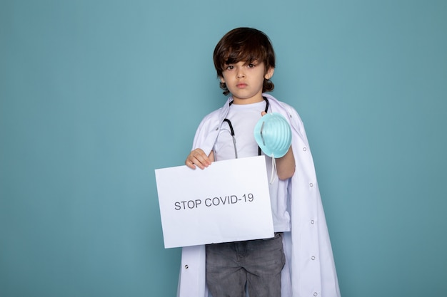 Child boy holding stop covid hashtag in white medical suit and grey jeans on blue wall