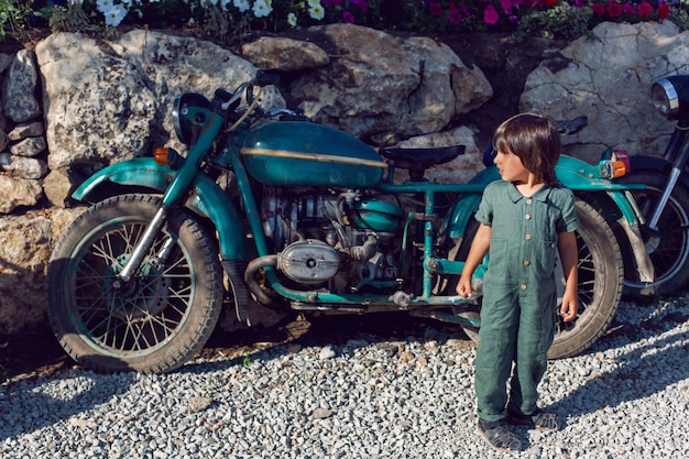 緑のジャンプスーツを着た男の子が夏に古いバイクの間を歩く