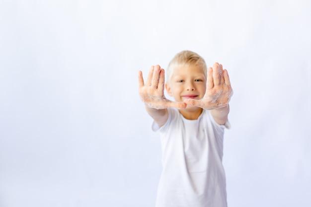 白いtシャツの子供男の子は泡で手を示しています
