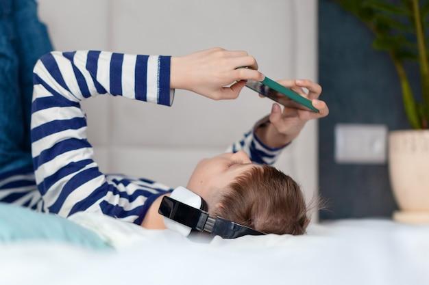 헤드폰을 끼고 전화를 하고 거실에 있는 침대에서 학습하는 어린 소년. 기술을 사용하는 개념 아이