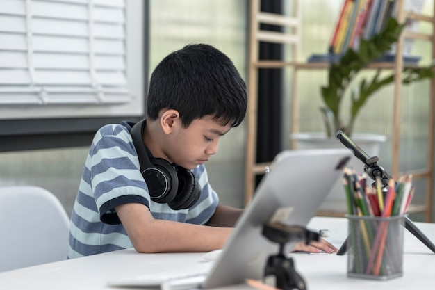 ヘッドホンをつけた男の子はタブレットを使っており、自宅でインターネット上で通信しています。ホームスクーリング、遠隔教育、オンラインでクラスを受講しているアジアの少年、ホームスクーリング検疫に満足しています。