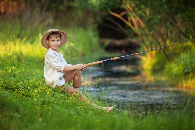 소박한 옷과 고리 버들 세공 모자에 아이 소년 그의 손에 낚 싯 대와 앉고 강둑에 물고기를 잡는 다. 남자를위한 취미와 여가