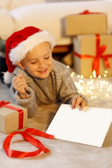 クリスマスの装飾のコピースペースの空白の近くに自宅でサンタに手紙を書くサンタ帽子の子少年