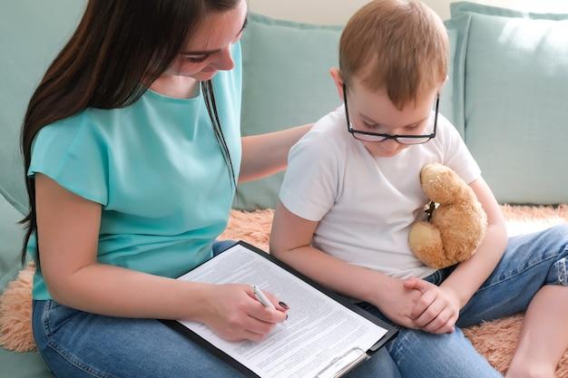 心理学者のオフィスの男の子。子供と話している心理学者、学生の問題