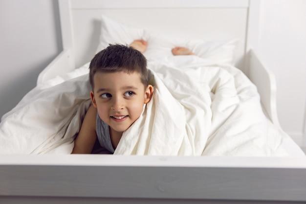 어린 소년은 어린이 방에 있는 흰색 침대에서 즐겁게 놀고 있다