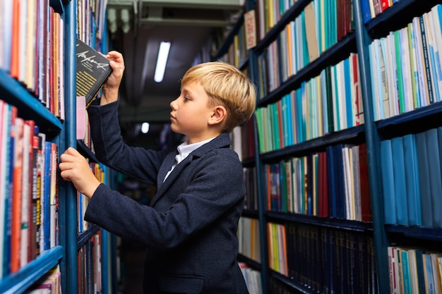 Child boy is searching and choosing book in bookshop, stand near shelves, going to learn and study