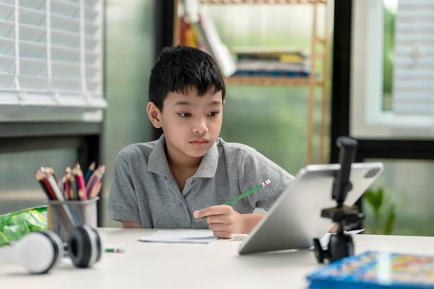 子供の男の子は自宅でインターネット上の通信を使用しています。ホームスクーリング、遠隔教育、