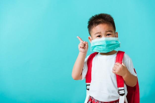 Детский садик ребенка носит защитную маску и школьную сумку перед походом в школу