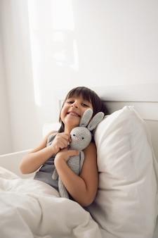 Ребенок мальчик лежит в белой детской кровати с одеялом в комнате с игрушками кролики обнимаются