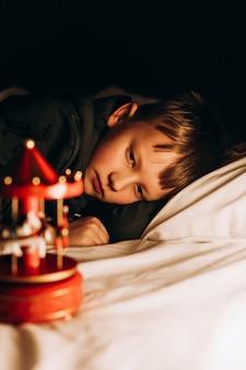 Ребенок мальчик ночь в спальне ждет волшебных снов санта-клауса