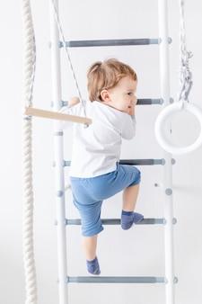 스웨덴 벽이나 스포츠 단지에있는 어린 소년은 집에서 올라갑니다. 어린이 스포츠의 개념