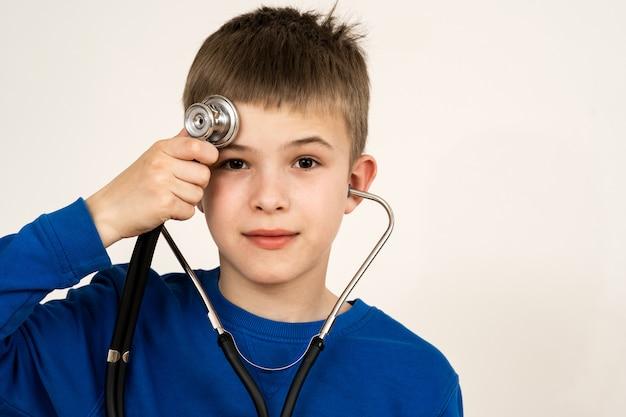 Ребенок мальчик играет врач со стетоскопом в руках