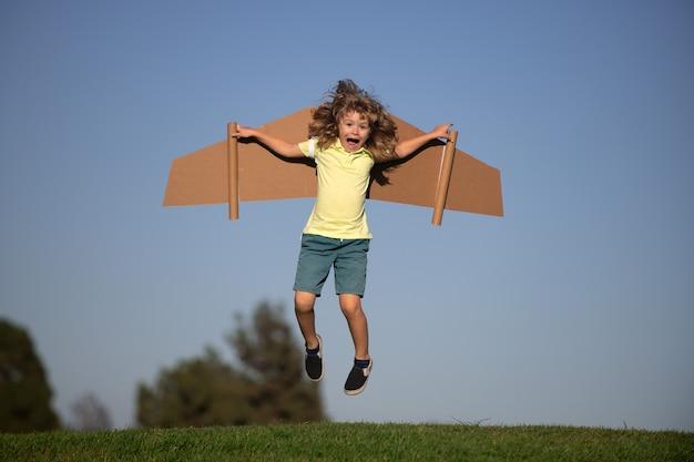Ребенок мальчик играет пилот на небесно-голубом фоне. малыш мечтает. ребенок играет с игрушечным реактивным ранцем. малыш-пилот веселится в парке. портрет ребенка против летнего неба. концепция путешествий и свободы.