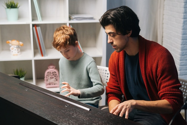 Child boy playing synthesizer at home during lesson music teacher sitting near and helps