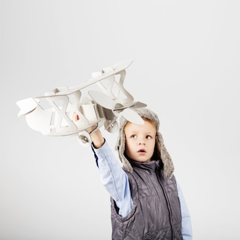 Child boy playing with paper toy airplane and dreaming of becoming a pilot