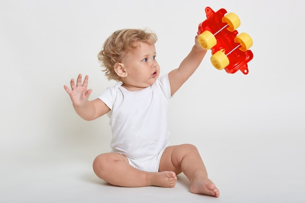 Child boy playing with toys indoors, sitting on floor and raising hands up, holding red and yellow toy car, looking at it with big eyes