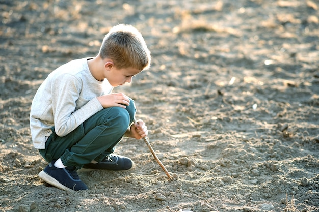 Child boy playing with wooden stick digging in black dirt ground outdoors.