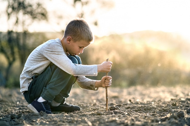 屋外の黒い土の地面を掘って木の棒で遊ぶ子供男の子。