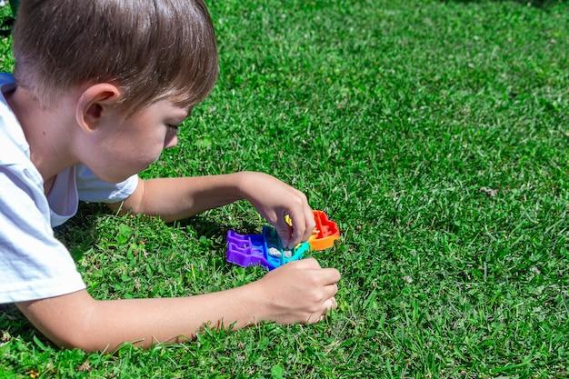 子供の男の子は公園の芝生の上でそれをポップで遊んでいます。青い泡のある新しい感覚発達玩具