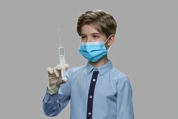 주입을 위해 주사기를 준비하는 아이 소년. 수술 마스크와 장갑 주입 주사기를 들고 백인 아이. 미래의 의사가되는 꿈.