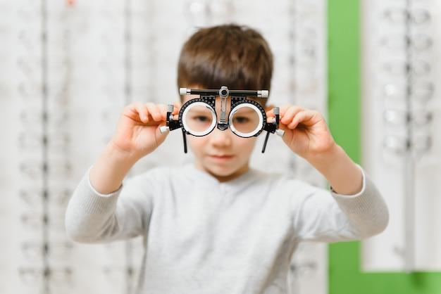 Детский мальчик, показывающий пробную рамку в офтальмологической клинике, выборочный фокус