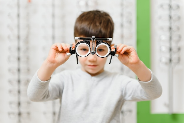Child boy showing trial frame in ophthalmology clinic, selective focus