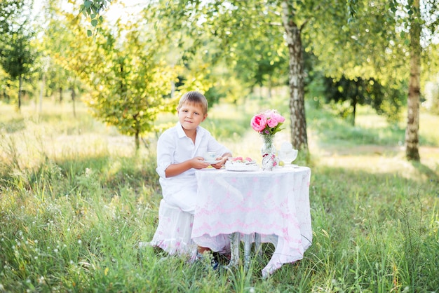 Child boy sitting at a table in nature . drinking tea