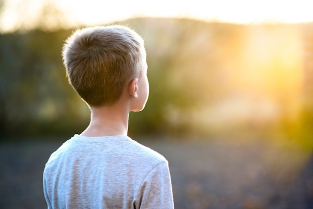 Child boy standing outdoors on summer sunny day enjoying warm weather outside