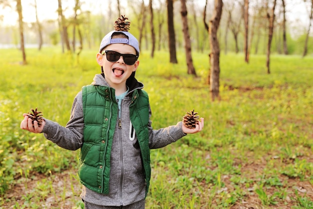 Child boy in sunglasses with bumps in his hands and on his head against the forest.