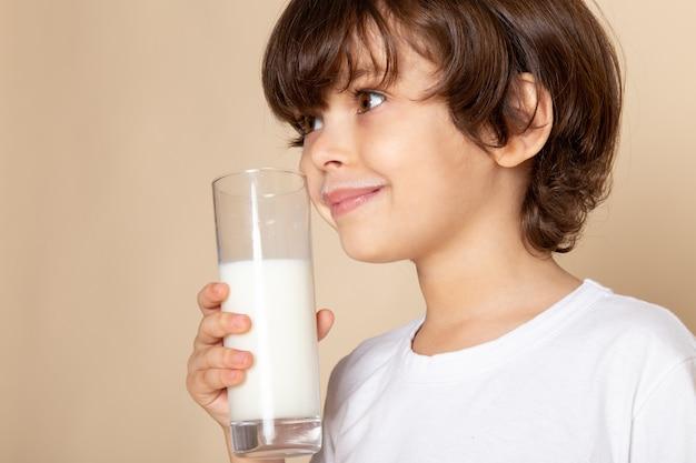 Bambino ragazzo dolce bere bianco latte intero su rosa