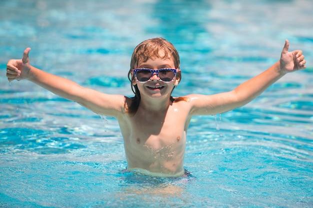 子供の男の子はプールで泳ぐ。夏の日のプールでサングラスをかけた興奮した子供。