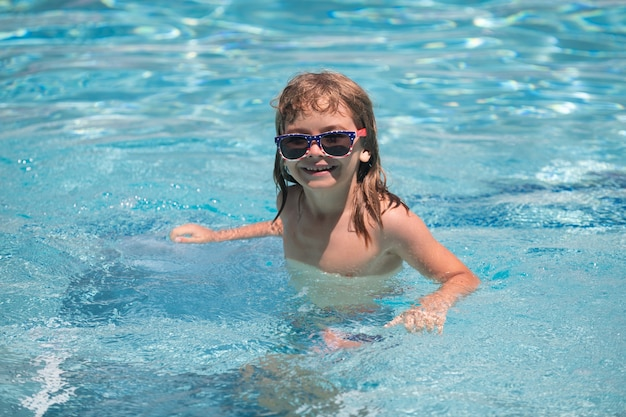 어린이 소년 수영장에서 수영. 수영장에서 어린이를 위한 여름철 및 수영 활동. 화창한 날 수영장에서 선글라스를 쓴 귀여운 소년의 초상화. 재미 있는 아이 얼굴.