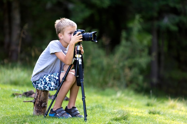 Child boy taking picture with tripod camera.