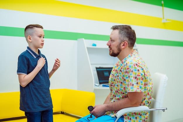 病院の医師の診察で症状を告げる男の子。