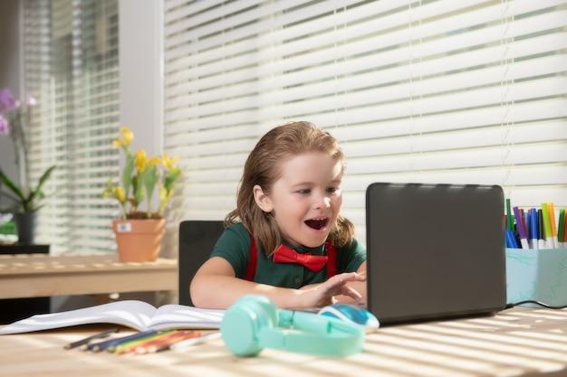 ノートパソコンを使用してオンラインレッスンを勉強する男の子。学校の生徒。ラップトップコンピューターを使用して、オンラインで勉強しているかわいい子供。