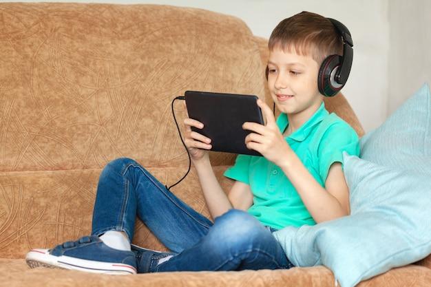 リビングルームのソファーにデジタルタブレットとヘッドフォンを使用して子少年。自宅で勉強してラップトップで遊ぶ子供